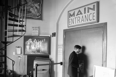 Black and white photo of a man entering doors.